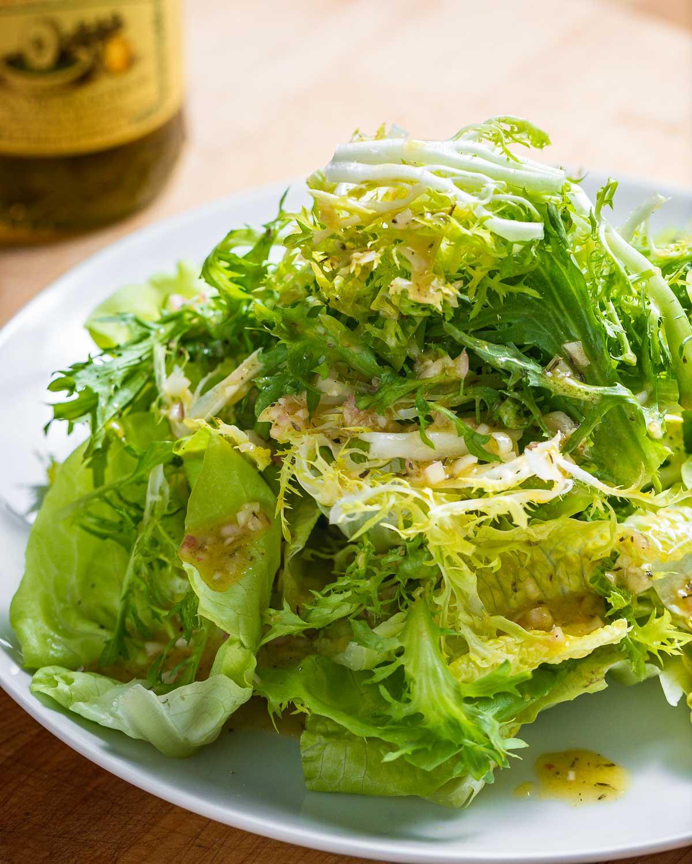 Plate of piled high lettuce greens with vinaigrette.
