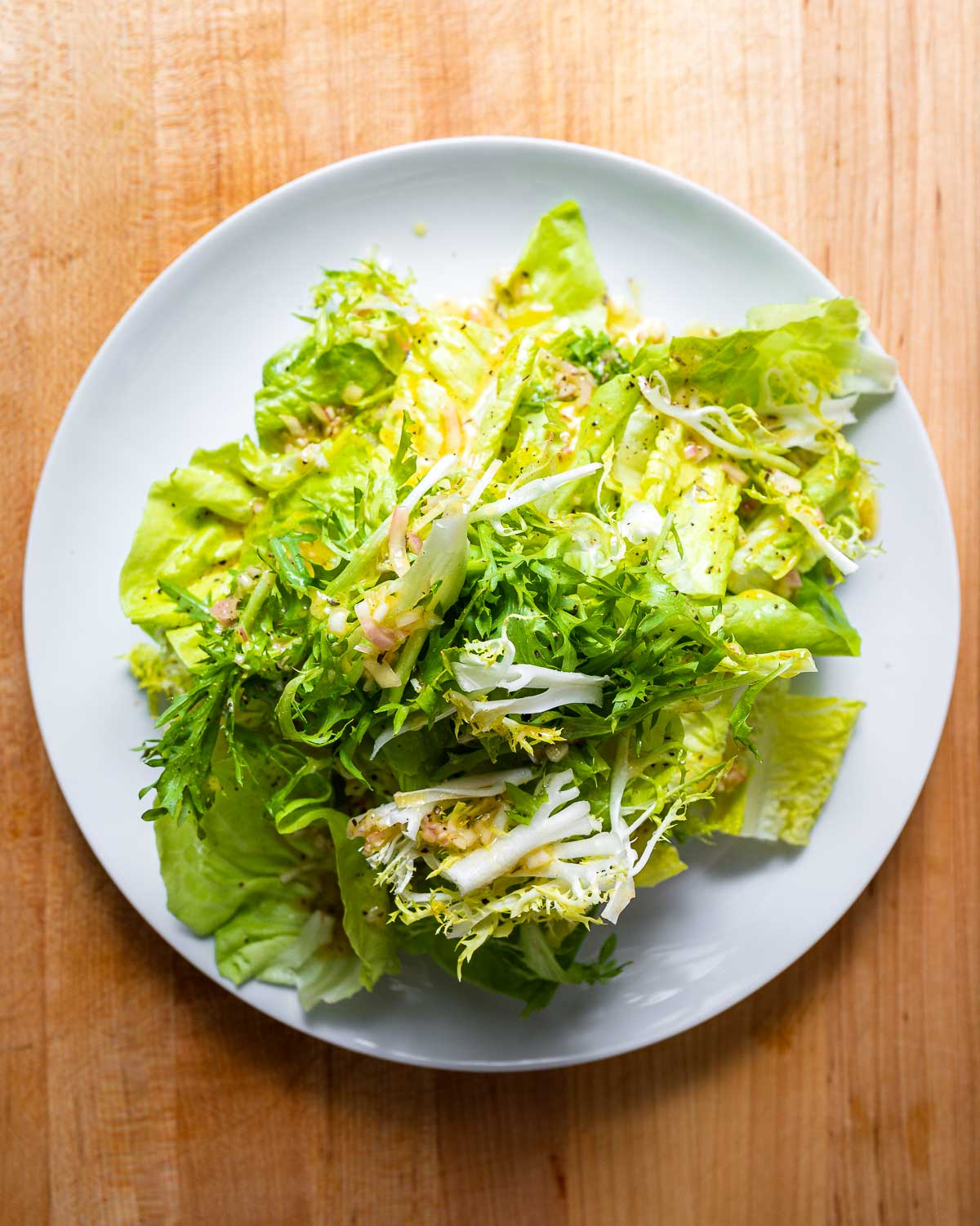 Overhead shot of white plate with 3 types of lettuce.