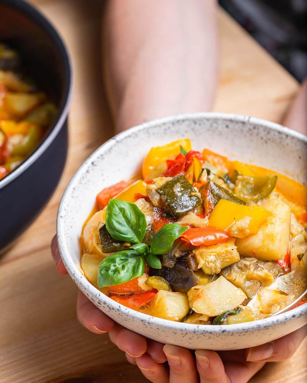 Italian vegetable stew in white bowl held in hands.