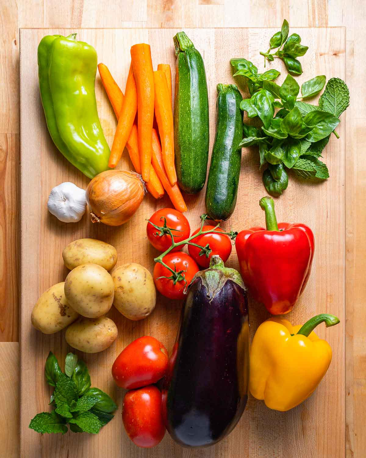 Vegetables shown: Peppers, carrots, zucchini, herbs, potatoes, tomatoes, eggplant, garlic, and onion.