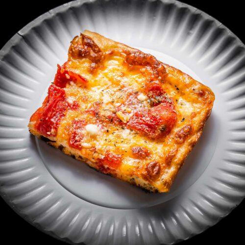 Grandma pizza slice in white plate featured image.