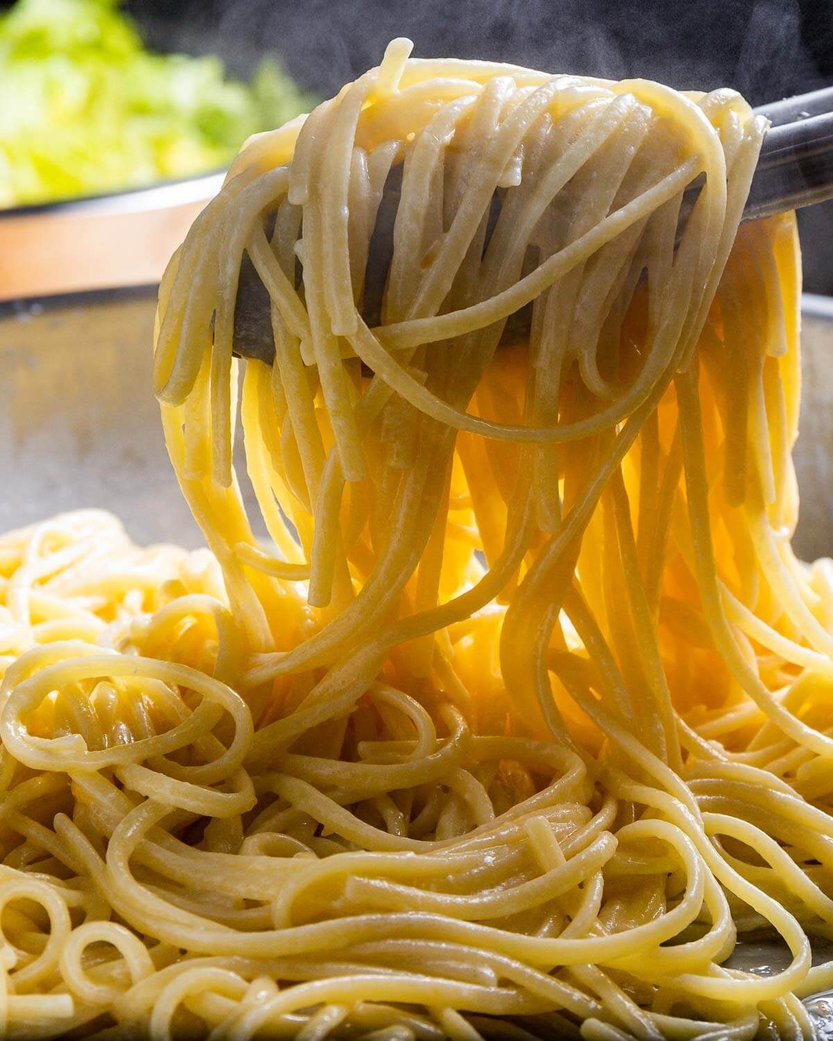 Tongs holding linguine with cheese.