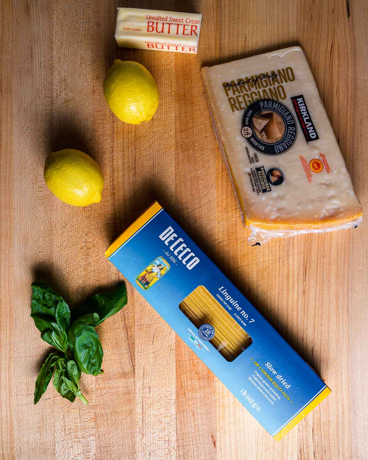 Ingredients shown: butter, lemons, parmesan cheese, basil, and box of linguine.