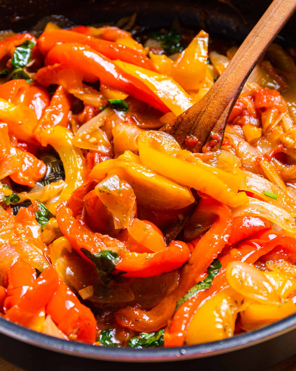 Peppers and onions in black pan with wooden spoon.