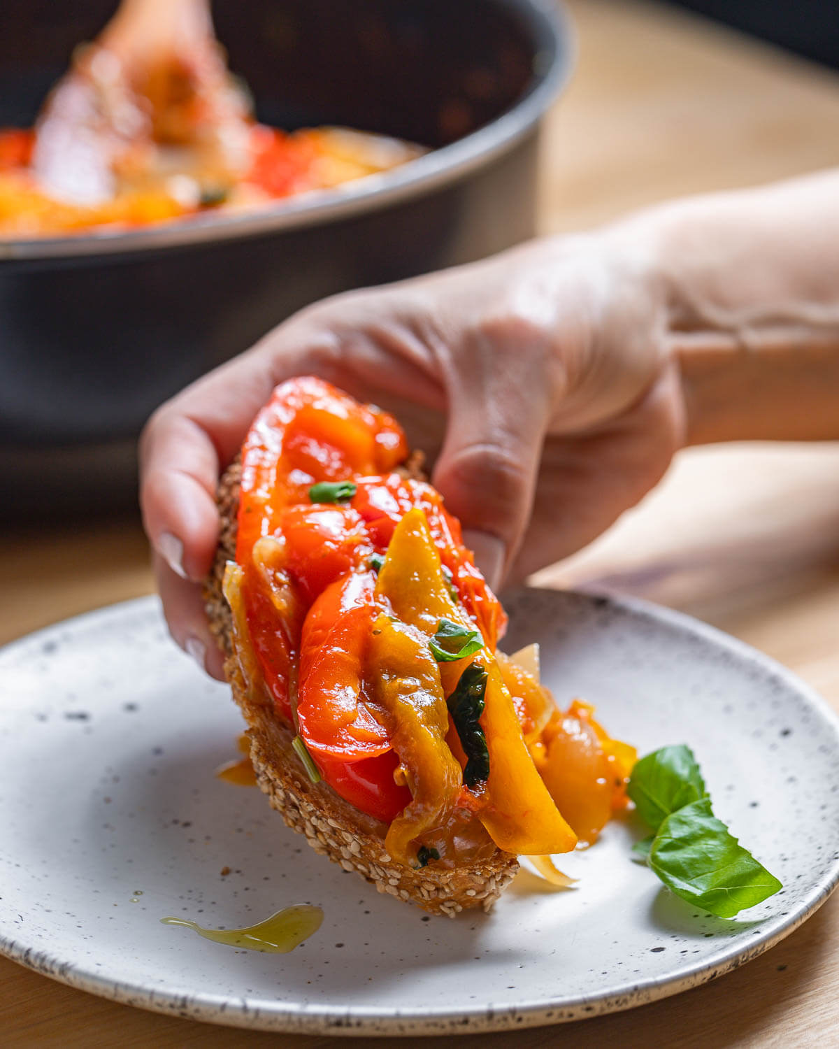 Toaste with peperonata held in hands over white plate.