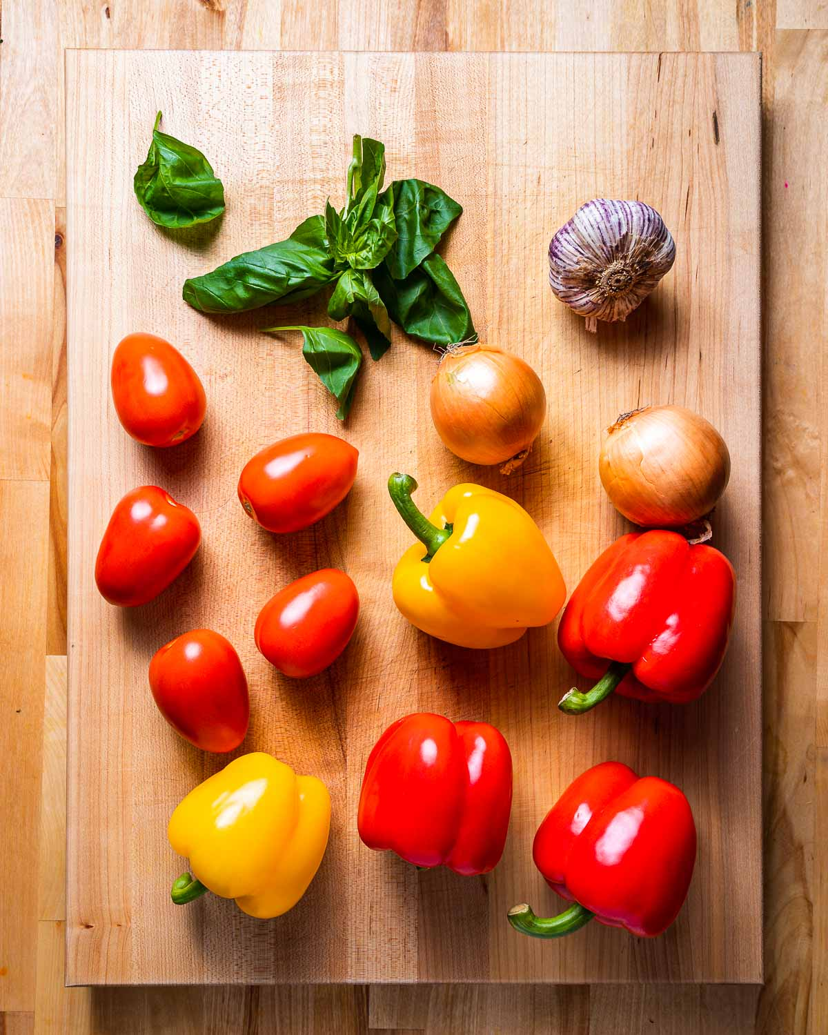 Ingredients shown: basil, garlic, tomatoes, onions, and bell peppers.