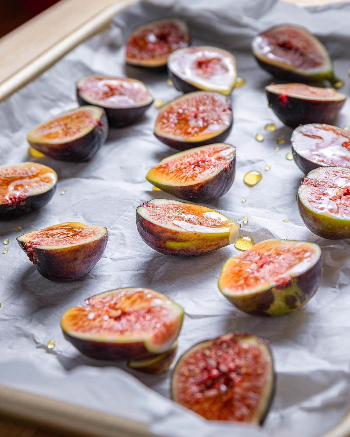 Cut figs on parchment paper lined baking sheet with drizzled honey.