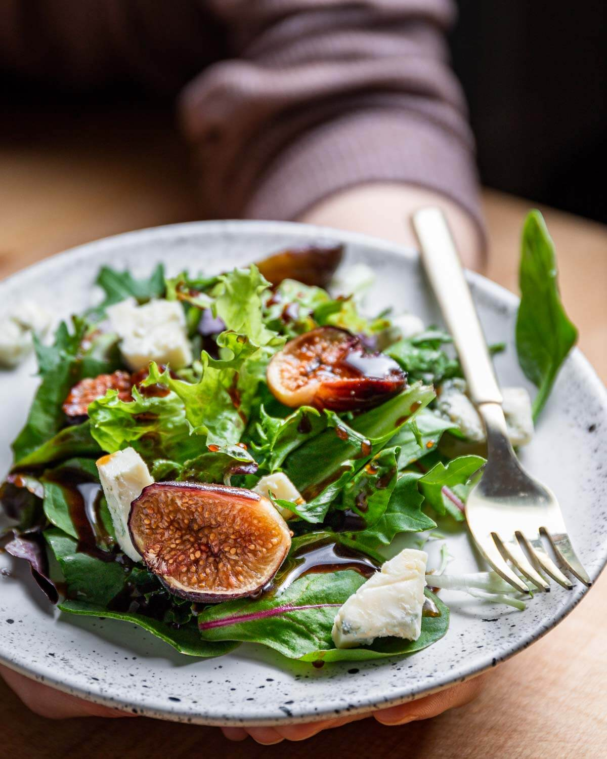 White plate with salad greens, gorgonzola cheese, and figs being held in hands.