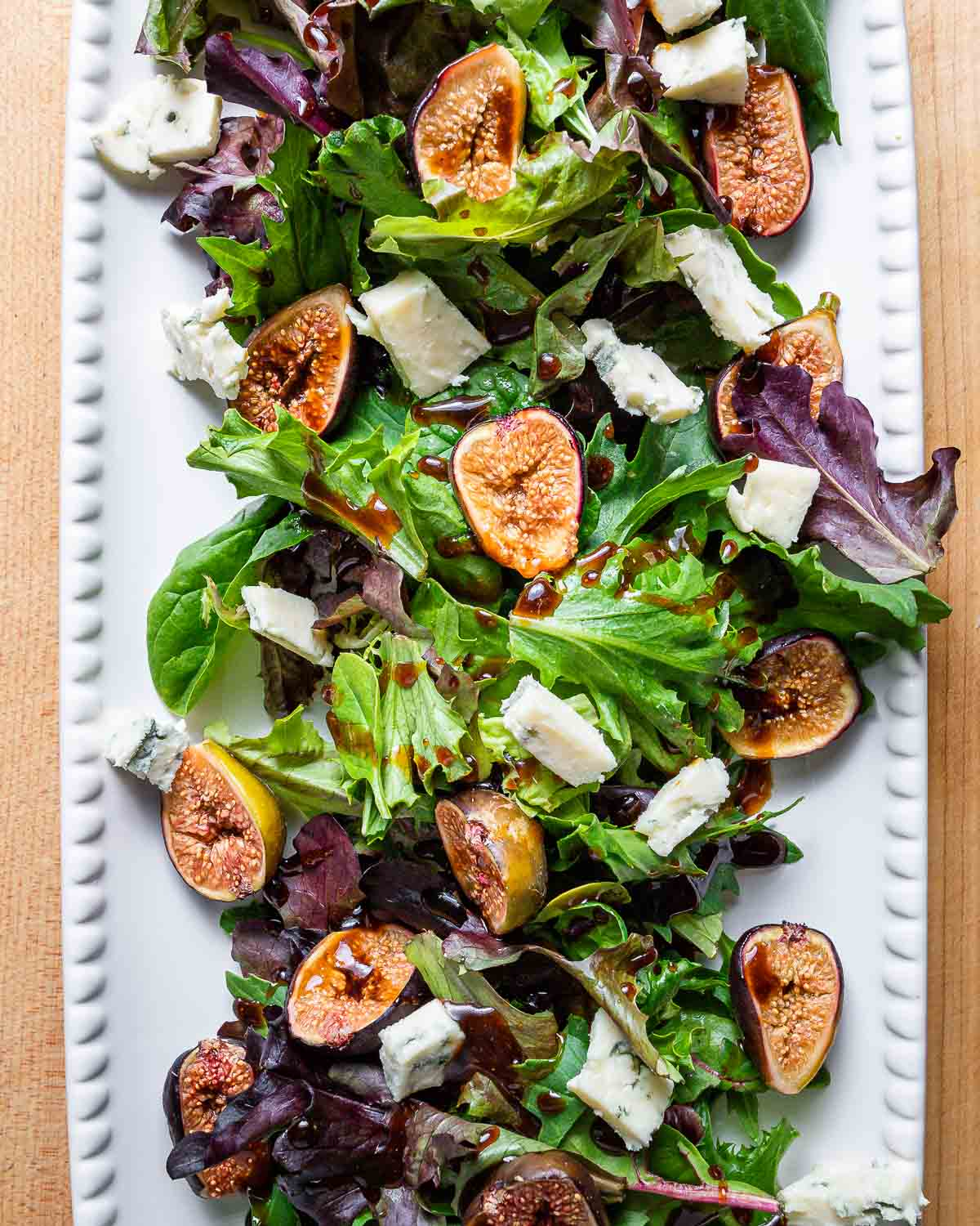 Overhead shot of large white platter with roasted fig salad.