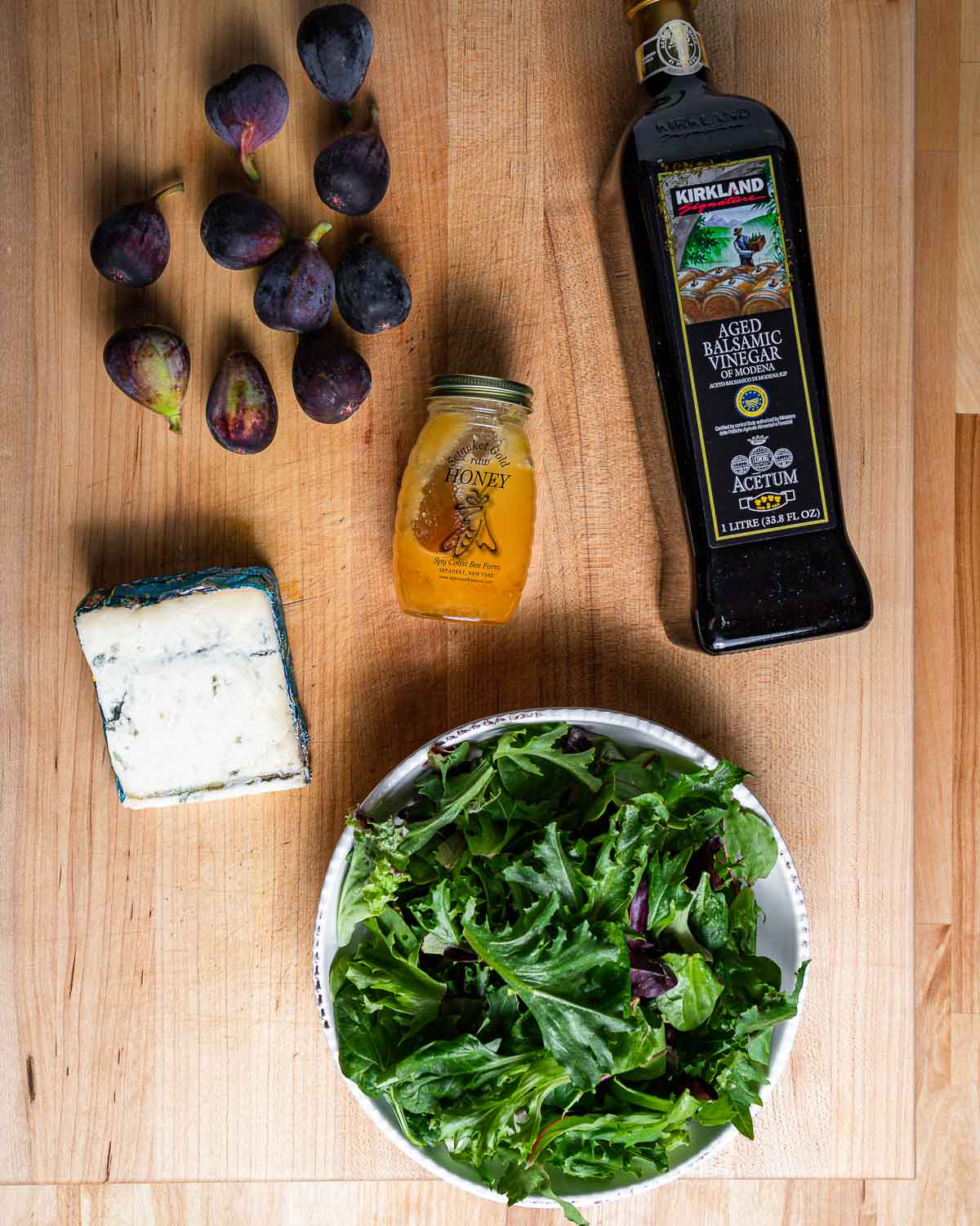Ingredients shown: figs, honey, balsamic vinegar, gorgonzola cheese, and mixed greens in bowl.