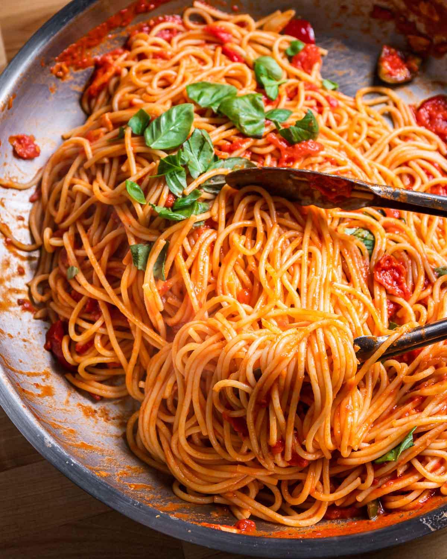 Spaghetti arrabbiata in steel pan with tongs.