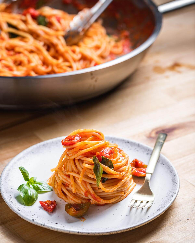 White plate of nested spaghetti arrabbiata.