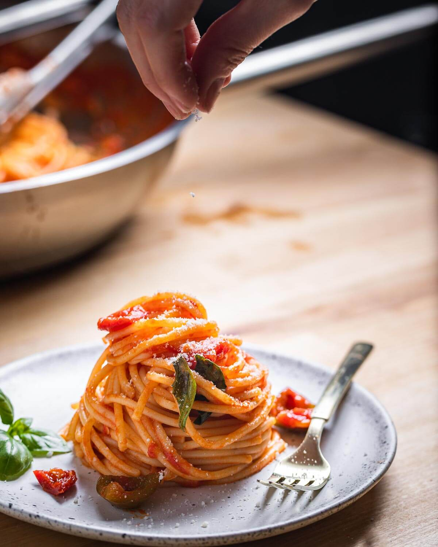 Sprinkling cheese onto plate of spaghetti.