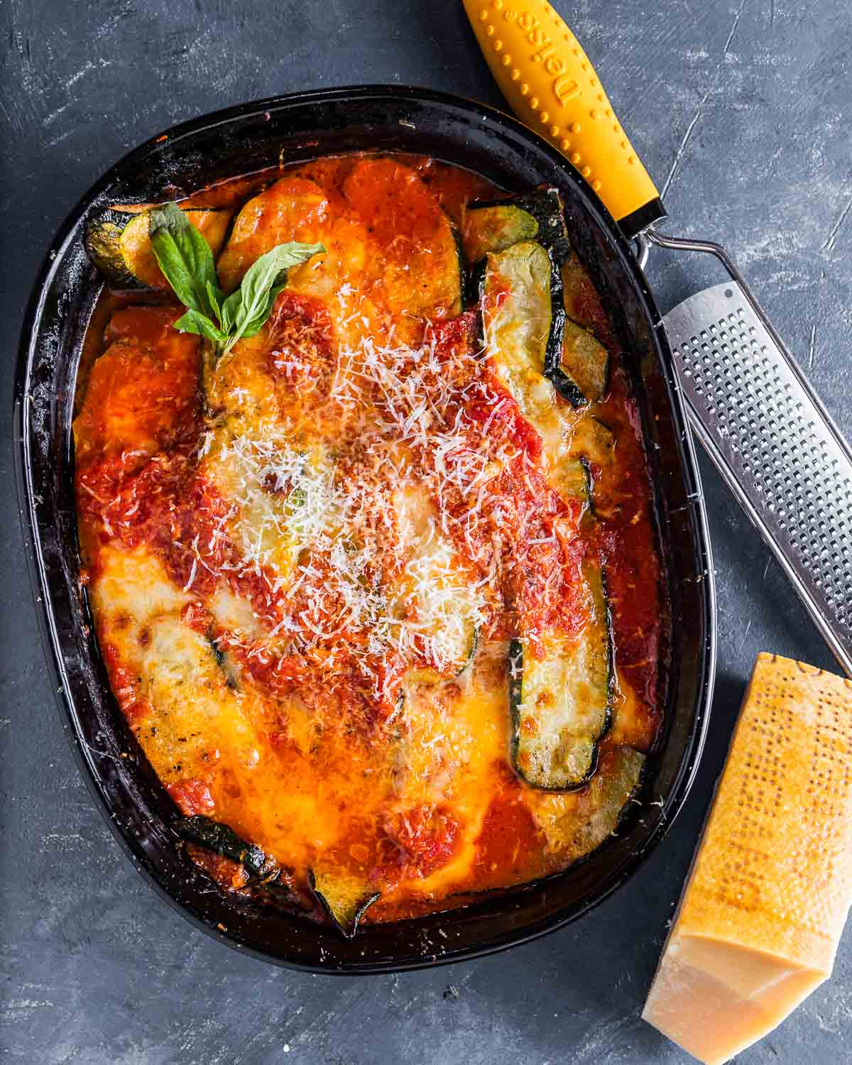 Overhead shot of baked zucchini parm in baking dish with block of Parmigiano Reggiano cheese on the side.