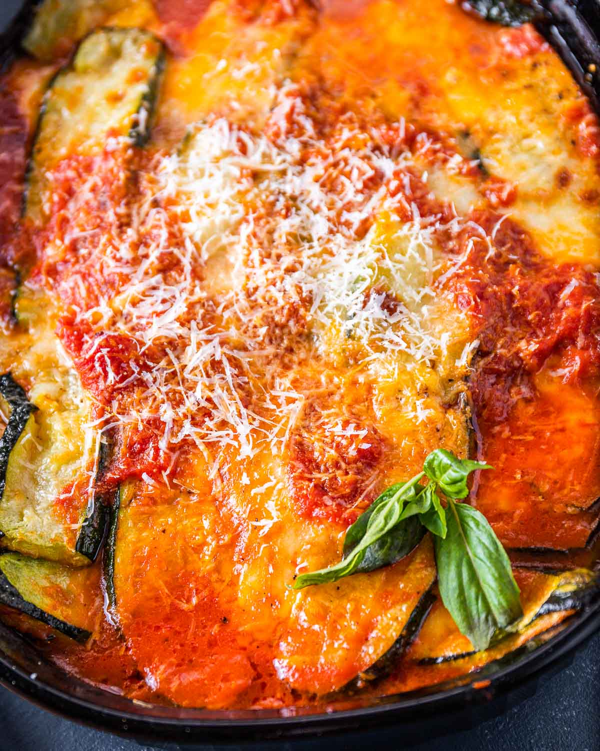 Black baking dish with cooked zucchini parm and basil garnish.
