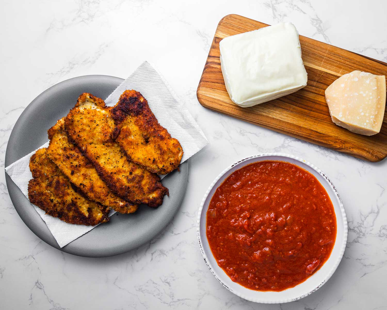 Ingredients shown: chicken cutlets, mozzarella cheese, parmesan cheese, and bowl of sauce.