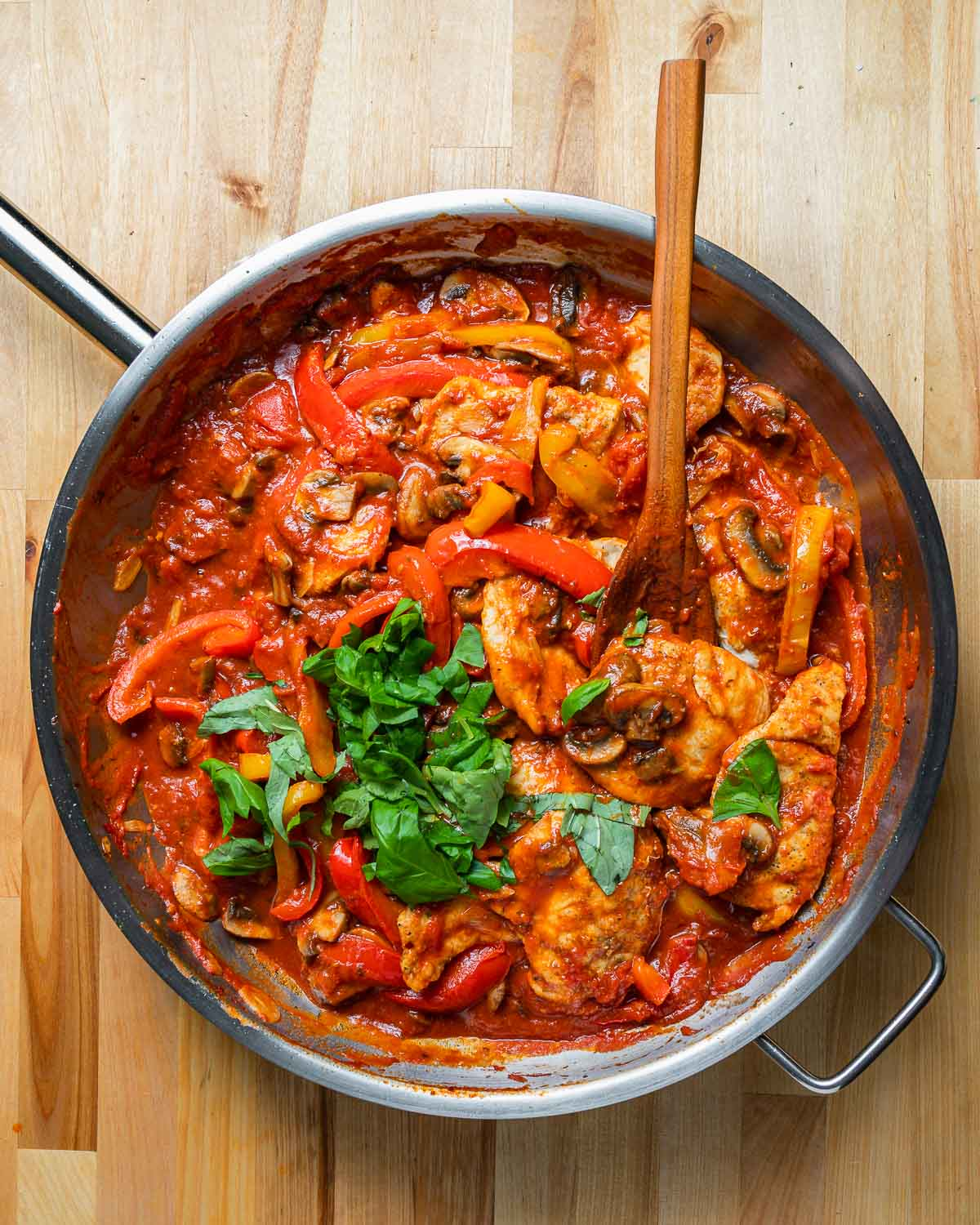 Overheat shot of large pan with chicken and peppers in tomato sauce.