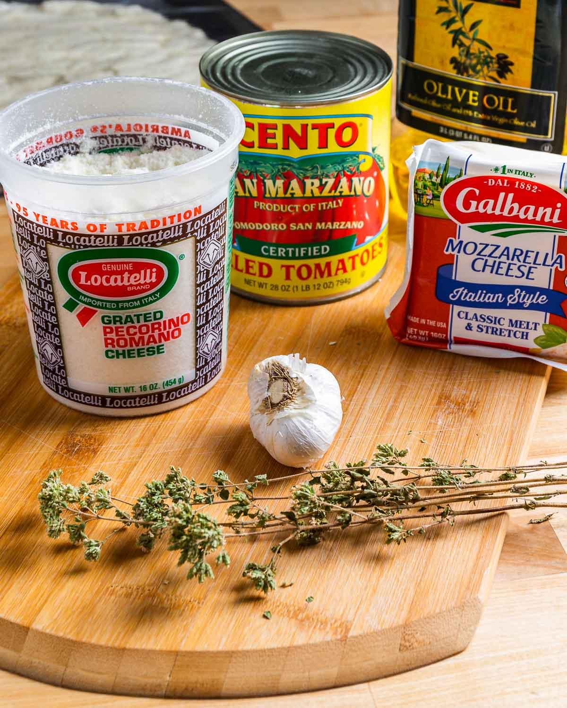 Ingredients shown: Locatelli Pecorino Romano, San Marzano tomatoes, mozzarella cheese, olive oil, garlic, and Sicilian oregano.