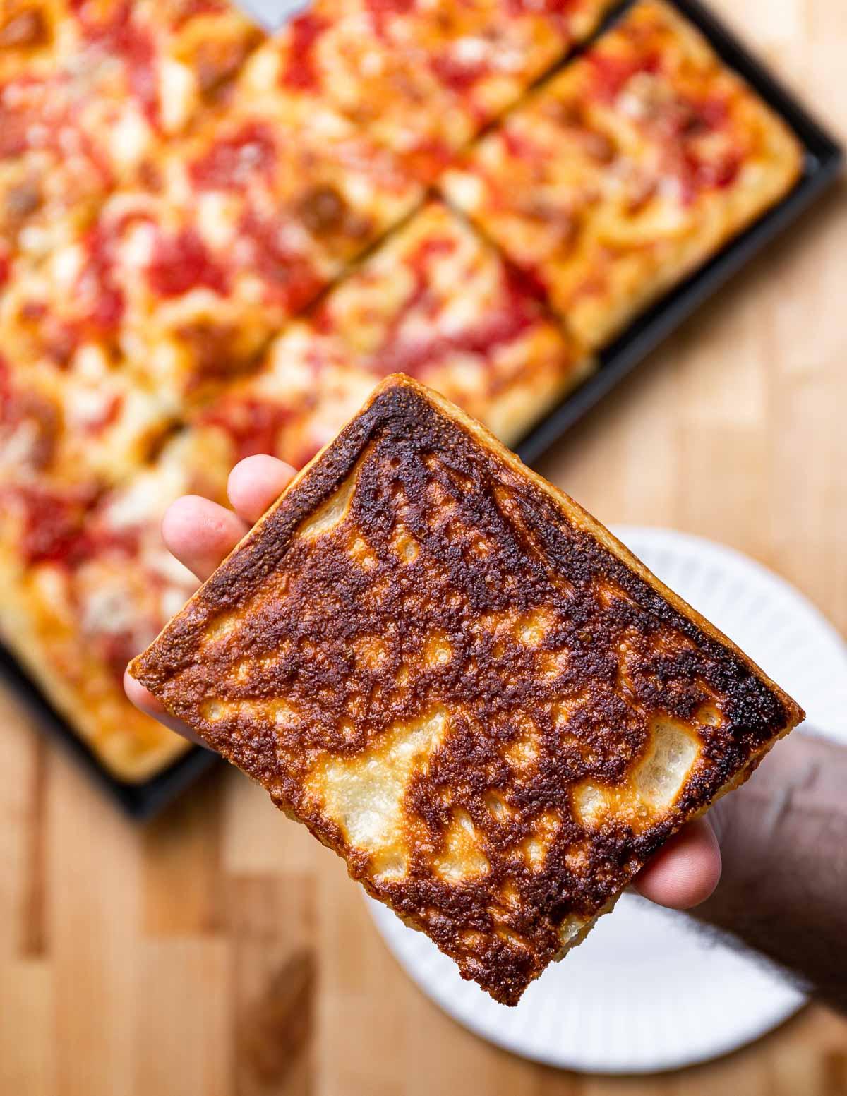 Crisp bottom of Grandma pizza held in hands.