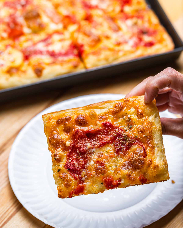 Grandma pizza slice held in hands.