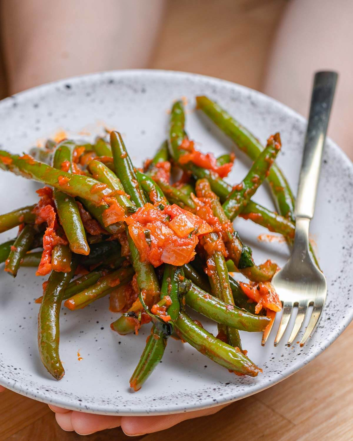Green beans with tomato sauce on white plate held in hands.