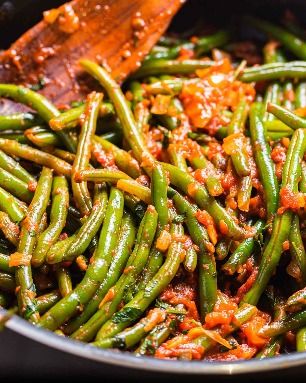 Pan full of green beans with tomato sauce.