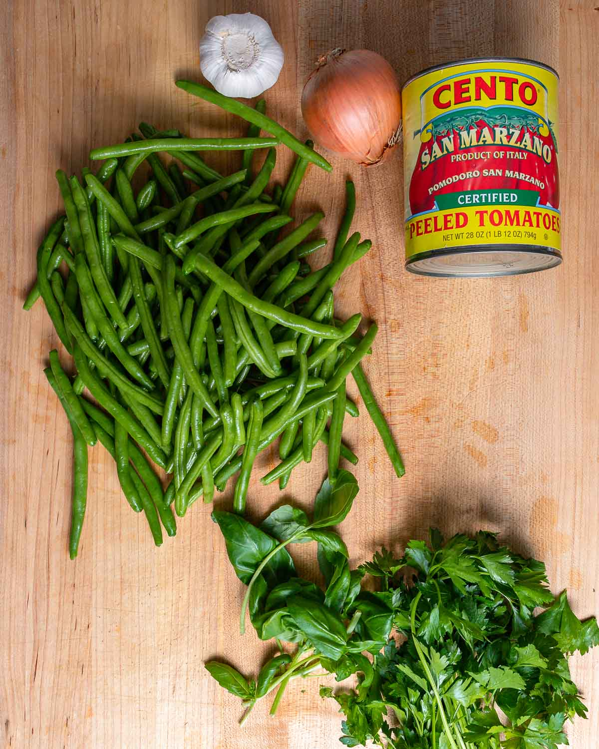 Ingredients shown: green beans, garlic, onion, can of plum tomatoes, basil, and parsley.