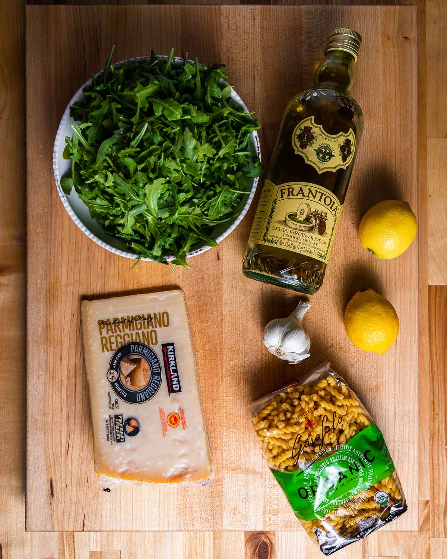 Ingredients shown: bowl of arugula, olive oil, parmesan cheese, lemon, garlic, and pasta.