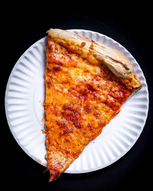 Slice of New York pizza in white plate.