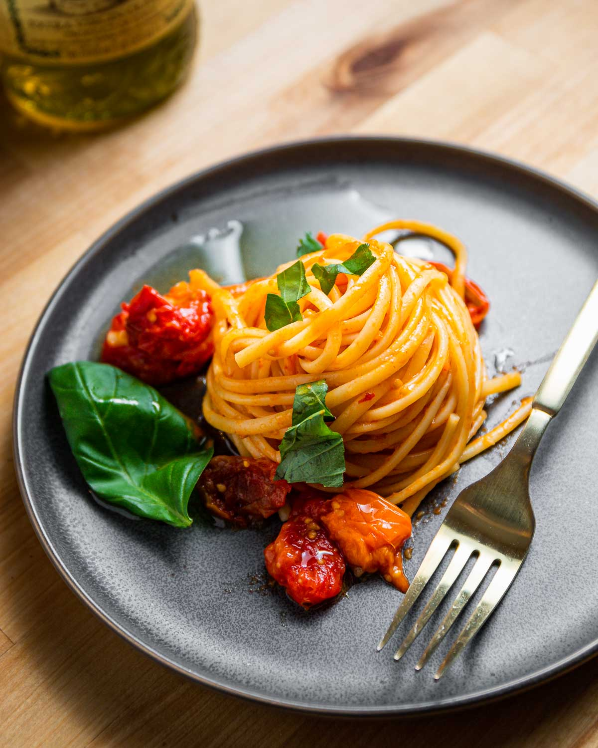 Grey plate with nest of linguine with roasted tomato sauce.