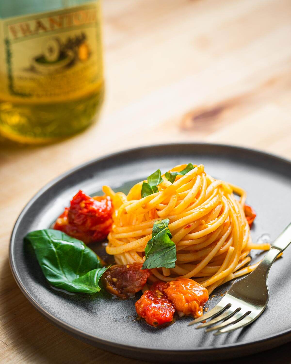 Grey plate with nest of linguine with roasted tomato sauce and bottle of extra virgin olive oil in background.