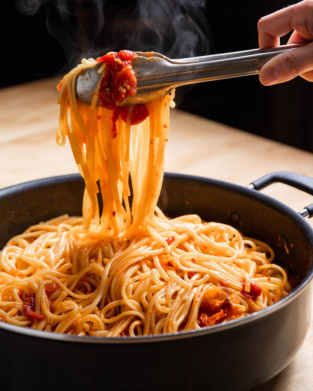 Tongs holding linguine with cherry tomato sauce over large pan.