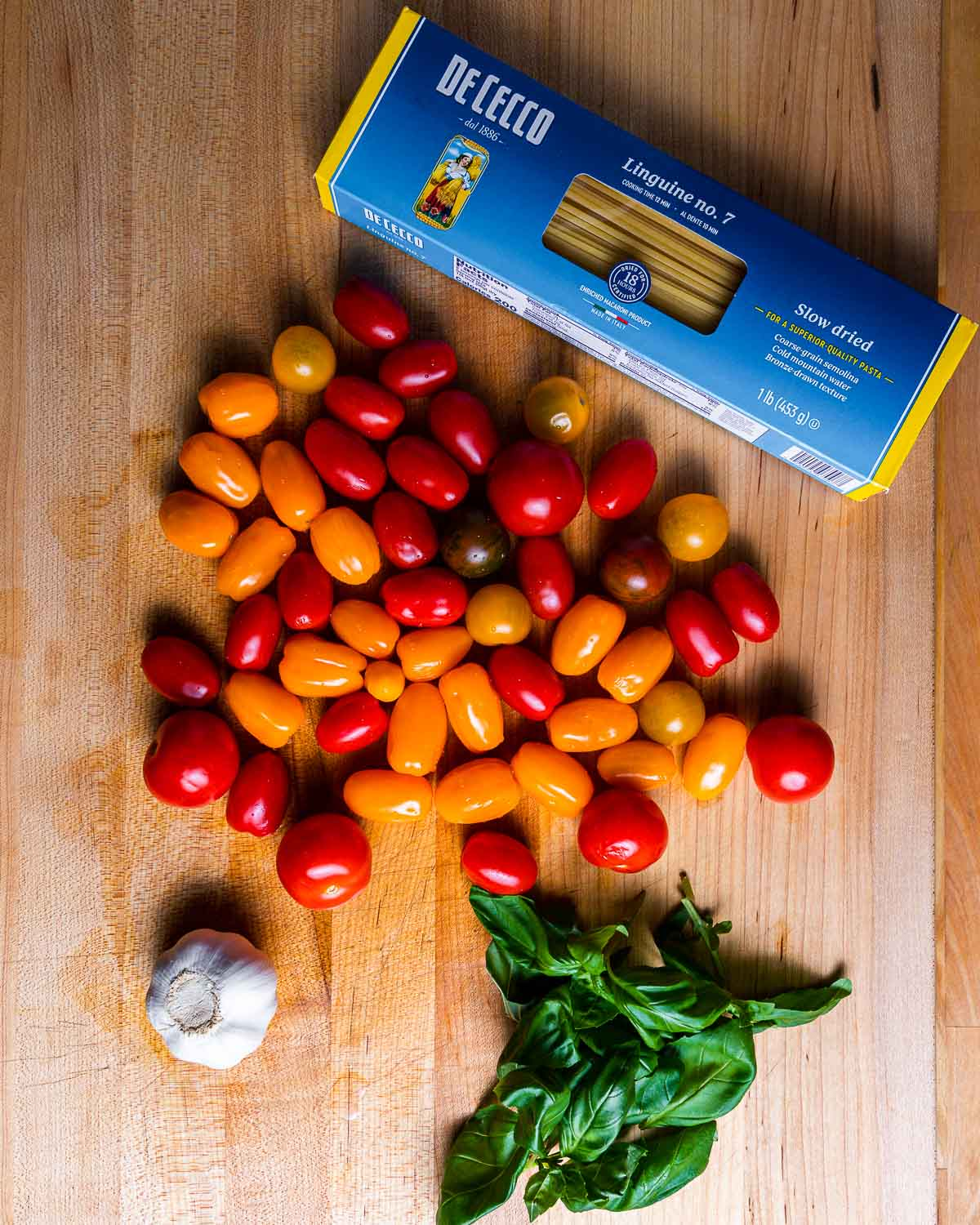 Ingredients shown: Linguine, assorted cherry tomatoes, garlic, and basil.