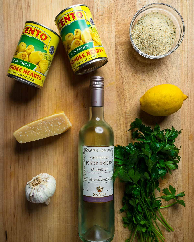 Ingredients shown: canned artichoke hearts, breadcrumbs, parmesan block, lemon, wine, garlic, and parsley.