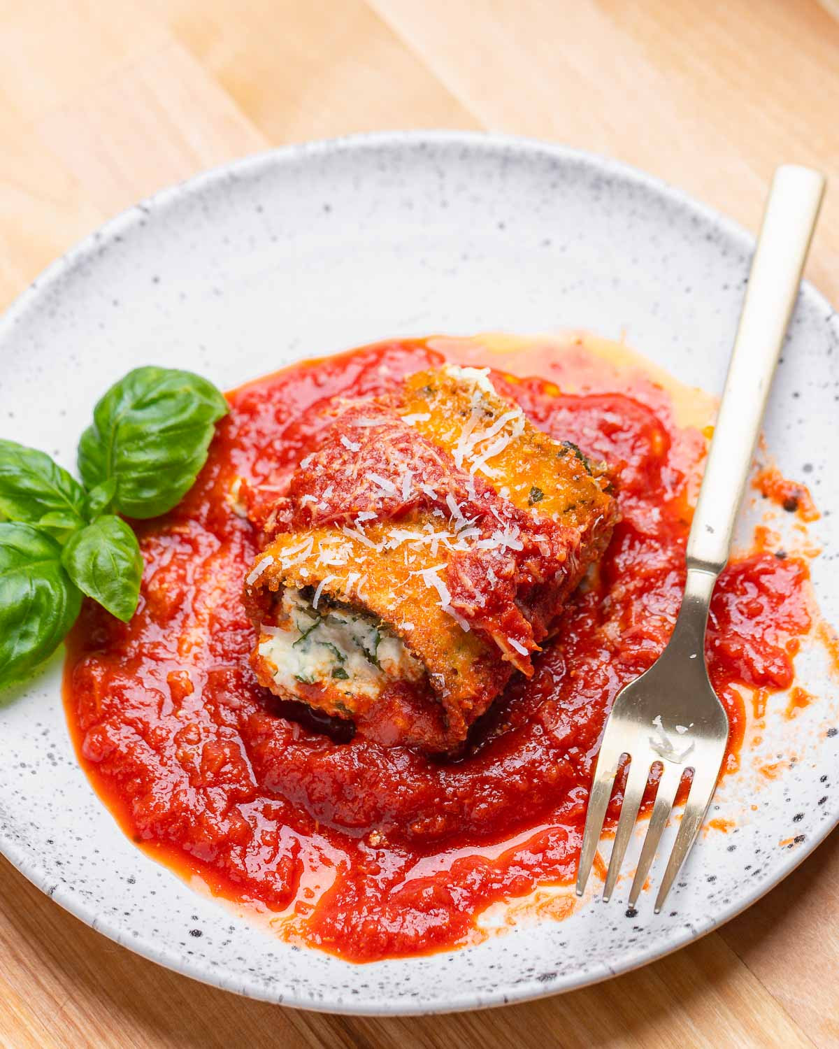 White plate with one eggplant rollatini, basil leaves, and fork.