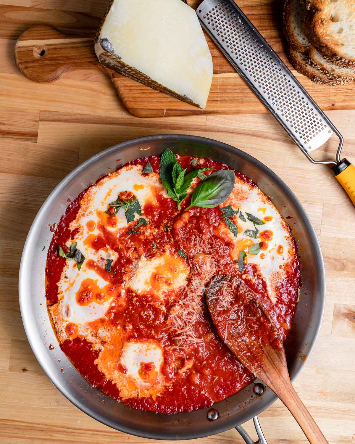 Pan of eggs in purgatory with cheese and bread on the side.