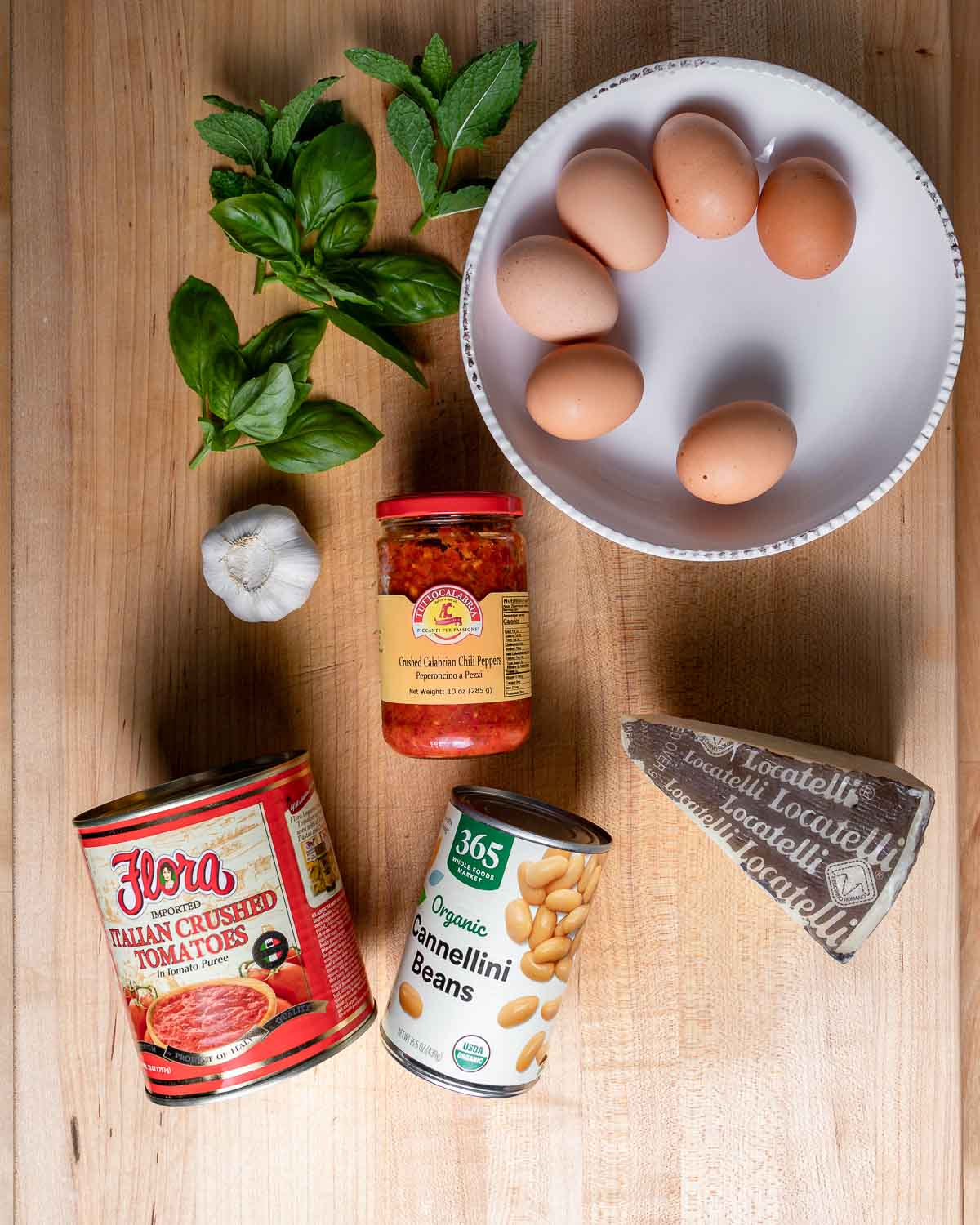 Ingredients shown: eggs, basil, mint, garlic, Calabrian chili paste, tomatoes, beans, and Romano cheese.