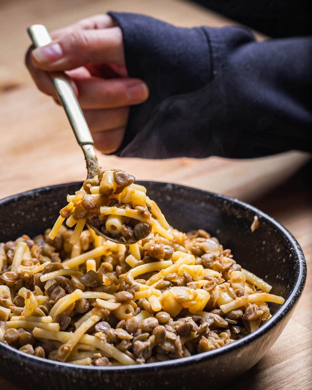 Hand holding spoonful of pasta e lenticchie.
