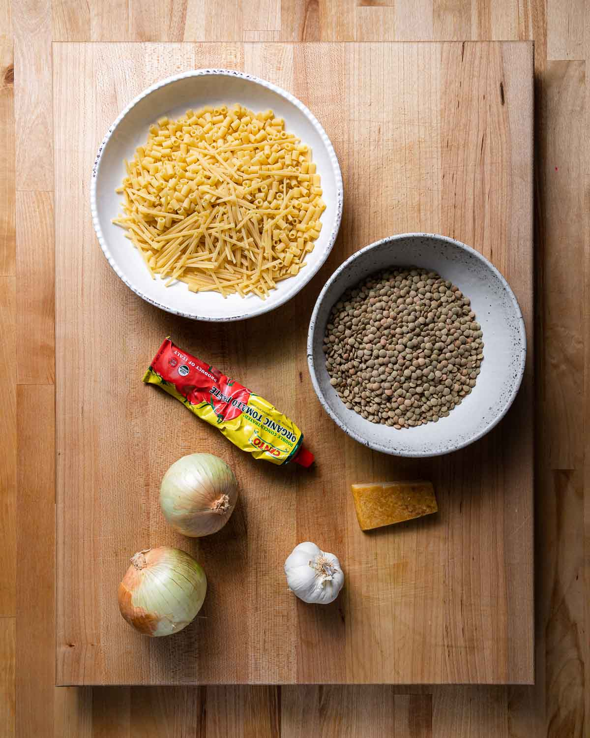 Ingredients shown: bowl of broken spaghetti and various pasta, lentils, tomato paste, onions, garlic, and parmesan rind.