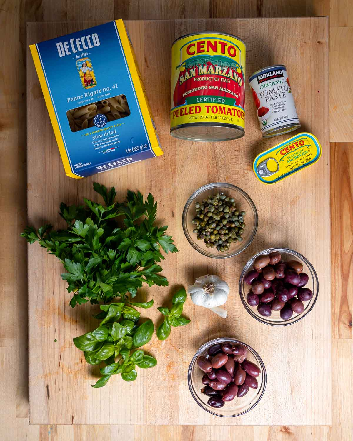 Ingredients shown: pasta, canned tomatoes, anchovies, capers, olives, garlic, herbs.