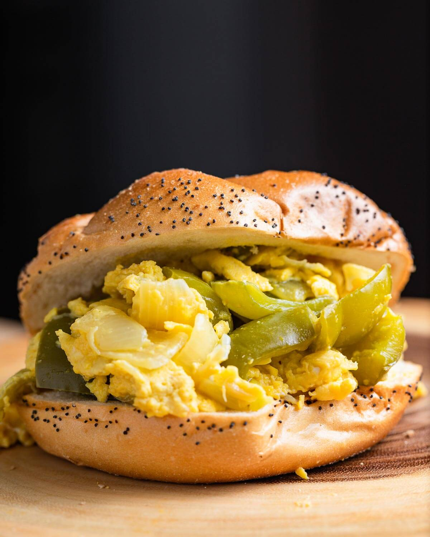 Pepper and egg sandwich on wood board.