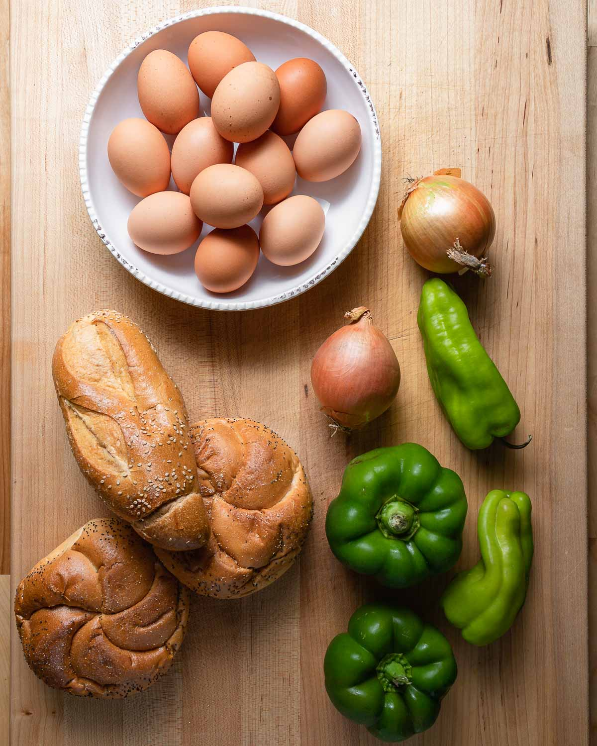 Ingredients shown: bowl of eggs, onions, peppers, hero and round rolls.