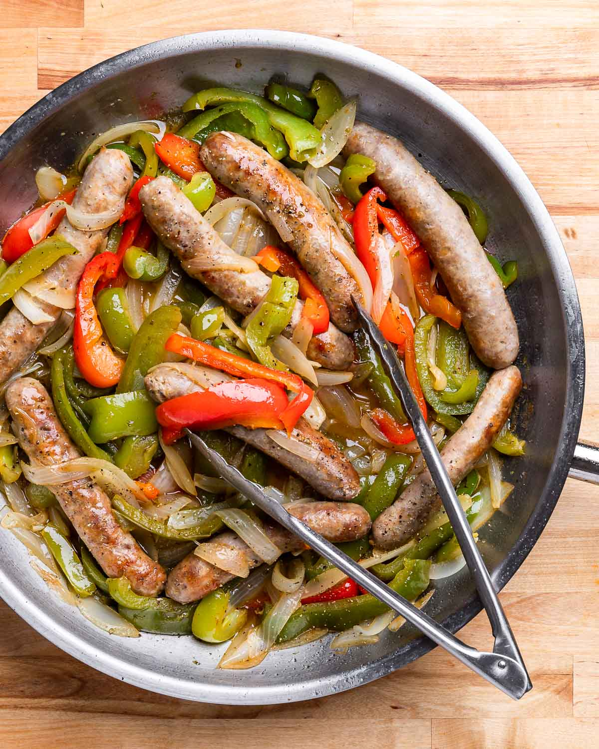 Large pan of sausage and peppers on wood table.