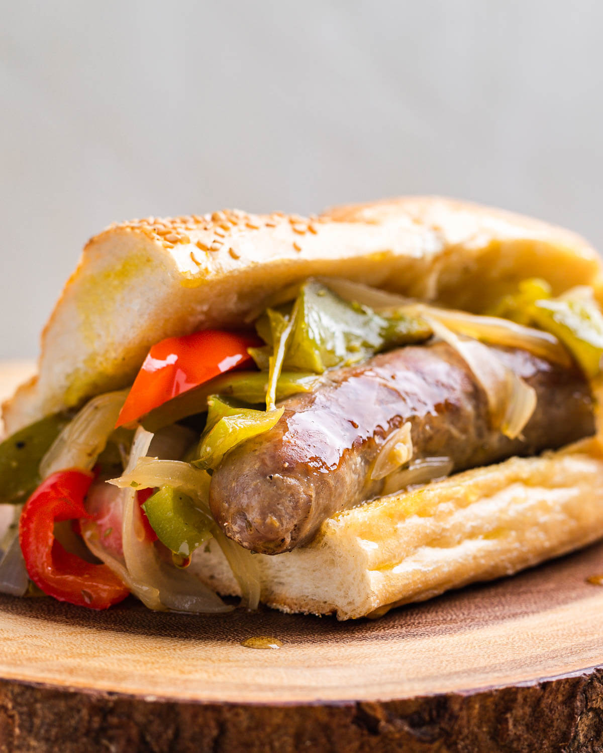 Sausage and peppers hero on wood board.