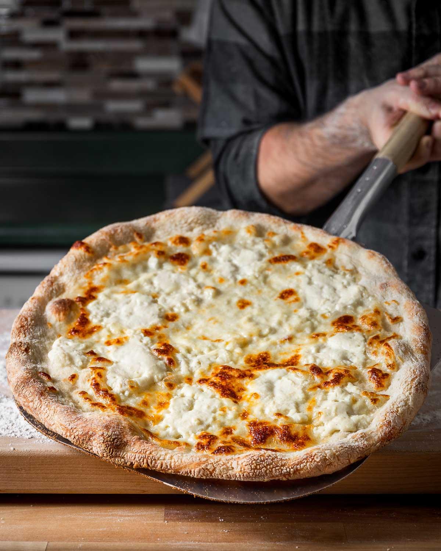 Full white pizza held by metal pizza peel.