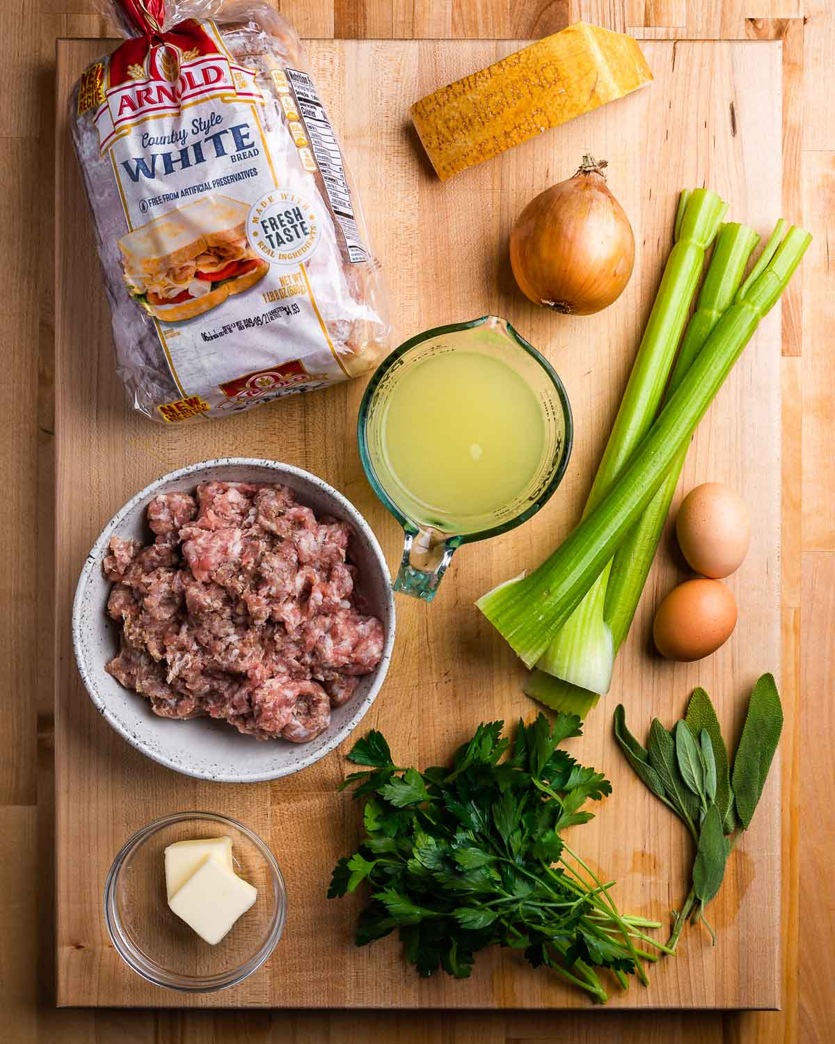 Ingredients shown: white bread, parmesan, onion, celery, chicken stock, sausage, butter, eggs, and herbs.