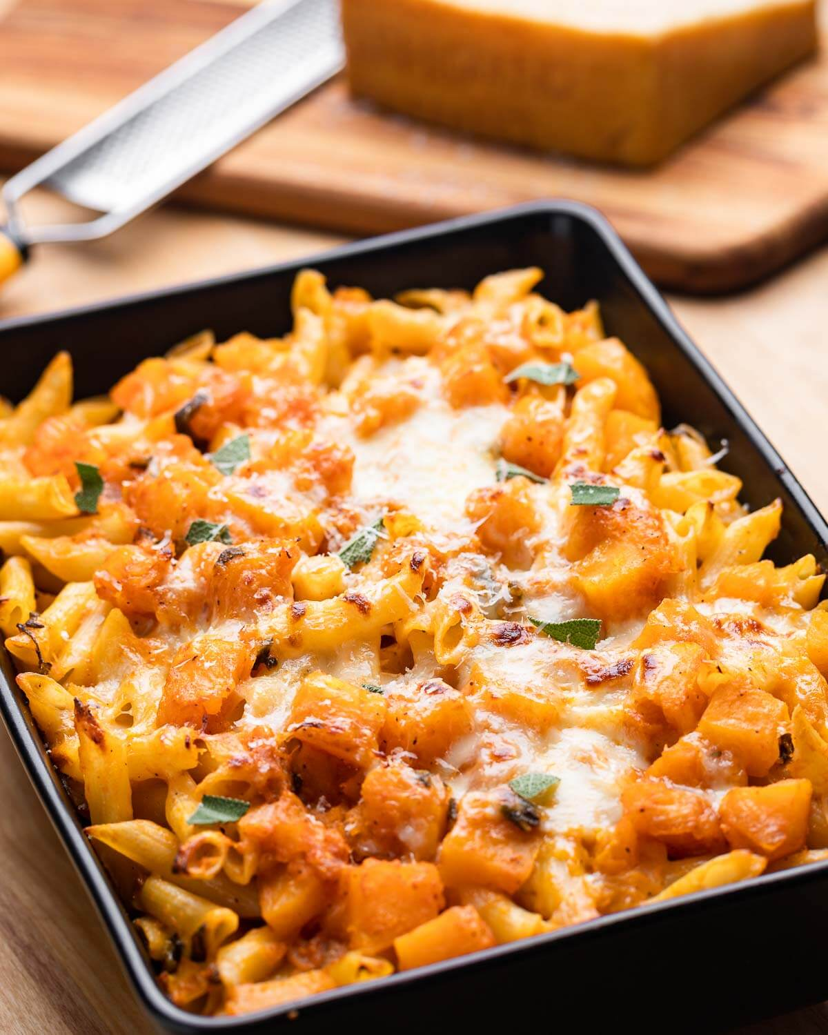 Baking dish with baked butternut squash pasta and block of Parmigiano Reggiano in background.
