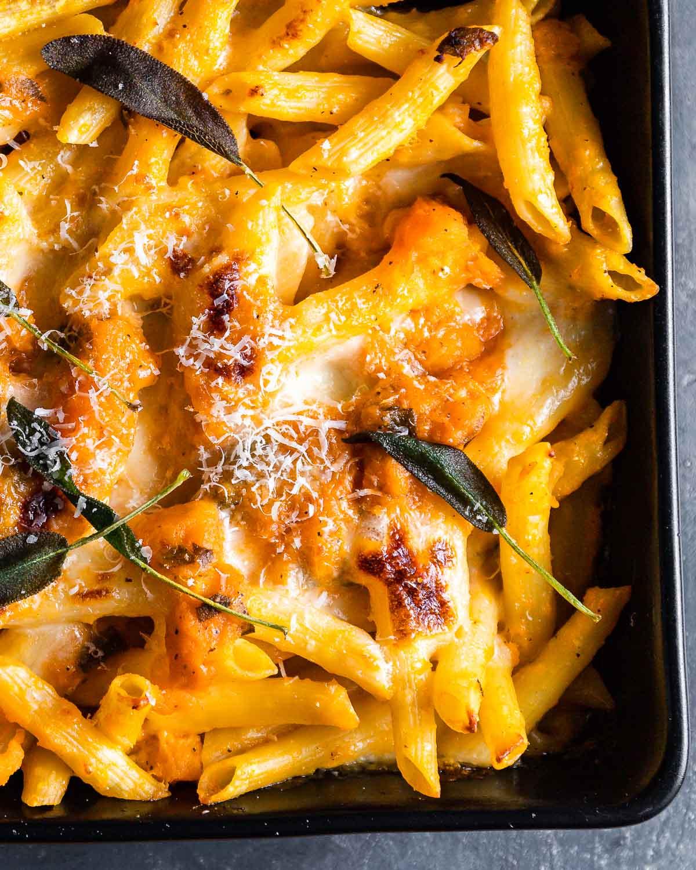 Close up shot of baked pasta with crispy sage leaves.
