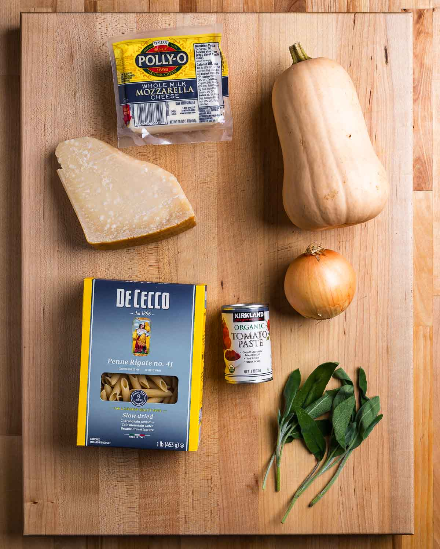 Ingredients shown: mozzarella, butternut squash, parmesan cheese, pasta, tomato paste, onion, and sage leaves.