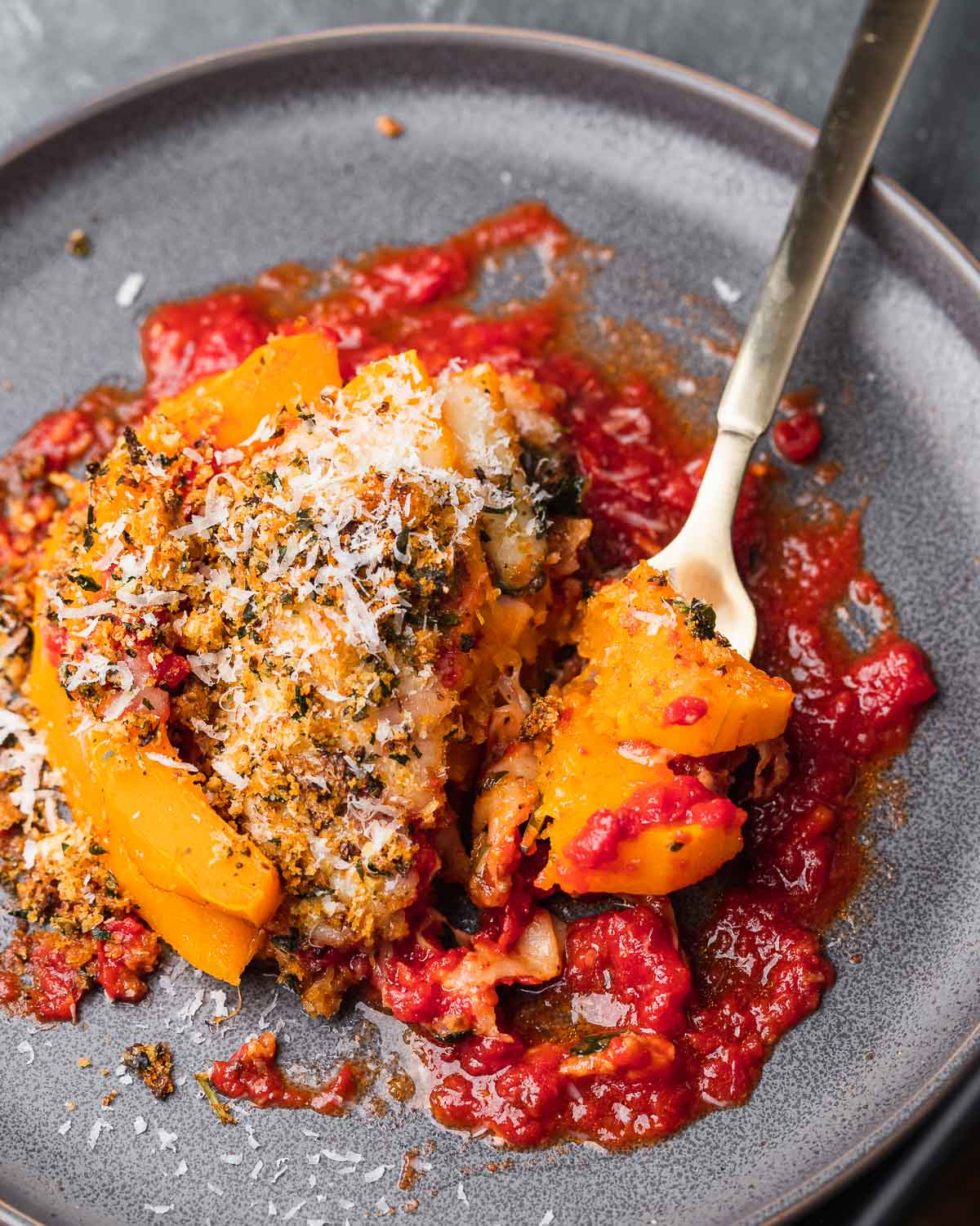 Butternut squash parmigiana in grey plate with fork holding piece.